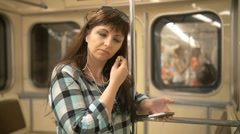Young woman inside underground listening to music with phone, slow motion Stock Footage