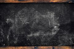 Chalk marks on dirty school blackboard with wooden frame Stock Photos