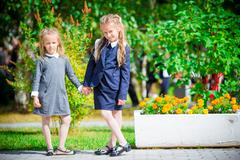 Two cute smilling little girls posing in front of their school. Adorable little Stock Photos