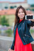 Young caucasian woman making selfie on attractions background outdoors. Happy - stock photo