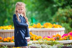 Cute smilling little girl posing in front of her school on first of September Stock Photos