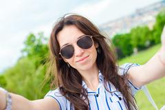 Young caucasian woman making selfie background european old city by mobile phone - stock photo