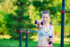 Beautiful young woman working out with weights outdoors. Active girl working out Stock Photos
