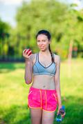 Young woman with apple after running outside. Female fitness model training Stock Photos