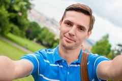 Young caucasian man making selfie background european old city by mobile phone - stock photo