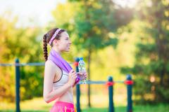 Young girl with botttle of water after running outside. Female fitness model - stock photo