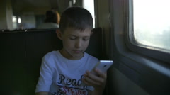 Boy travelling by train sitting in wagon using mobile phone, slow motion Stock Footage