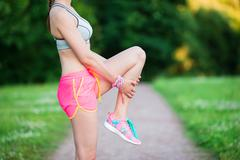 Active woman doing warm-up routine in the park before running, stretching leg Stock Photos