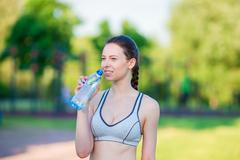 Young woman drinking water after running outside. Female fitness model training - stock photo