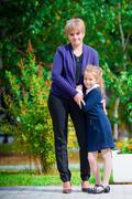 Grandmother brings her granddaughter to school. Adorable little girl feeling Stock Photos