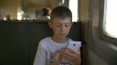 Young teenage boy travelling by train sitting in wagon using mobile phone, slow Stock Footage