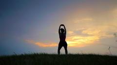 Healthy woman meditating in pose lotus over orange sun Stock Footage