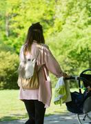 Happy mother walking with baby stroller in park Stock Photos