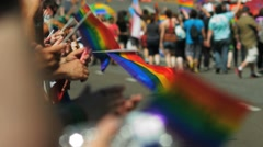People clap, cheer and hold wave rainbow flags as gay pride parade marchers walk Stock Footage