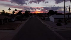 Fly through a suburban neighborhood at sunset following car - Tracking Stock Footage