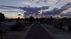 Fly through a suburban neighborhood at sunset - Tracking Backwards Stock Footage