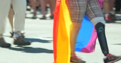 Person walking in Gay pride parade with prosthetic leg and rainbow flag on back Stock Footage