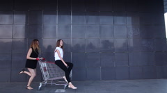 Girl runs, rolls friend in shopping cart sales - stock footage