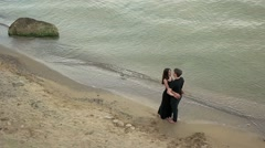 Couple in black clothing embracing by the sea Stock Footage