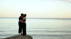 Couple in black clothing embracing on the rock by the sea Stock Footage