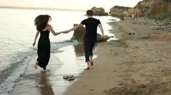 Couple running barefoot on the beach - stock footage