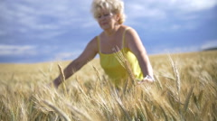 woman in a wheat golden field, hand stroking wheat, slow motion - stock footage