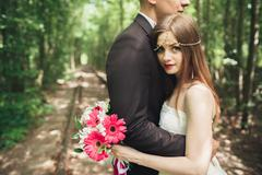 Romantic newlywed couple kissing in pine tree forest Stock Photos