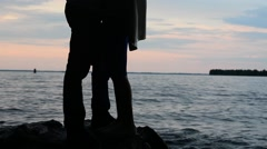 silhouette of a romantic couple on a sunset background near water - stock footage