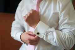 Man puts on his shirt cuffs Morning groom Accessories Stock Photos