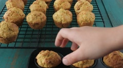 Child hand put mini Muffins cakes on cooling rack 4k Stock Footage