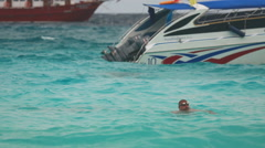 Man swimming near speedboat Stock Footage