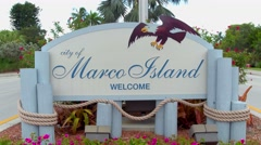 Marco Island welcome sign and American Flag Stock Footage
