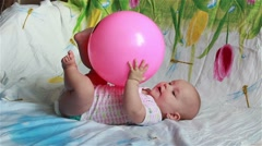 Charming baby is lying in bed and plays with a big red ball Stock Footage