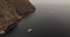 Sport Fishing Boat Anchored Off Rugged Island Coast Aerial Stock Footage