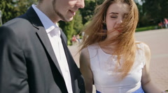 Happy young couple walking in a summer Park where the wind ruffles the girl's Stock Footage