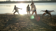 Dance performance of four girls on sand beach near lake at dawn Stock Footage