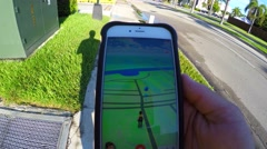 Playing pokemon go on iphone - stock footage