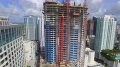 Aerial panning down highrise construction site Stock Footage