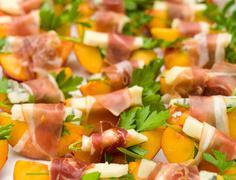 Many small peach and gorgonzola wrapped prosciutto snacks Stock Photos