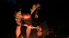 man checks the readiness of meat at the firelight by night - stock footage
