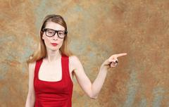 Young woman with eye glasses showing with her index finger place for copy space Stock Photos