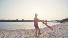 Happy mother whirls daughter holding hands on the beach at sunset, slow motion Stock Footage