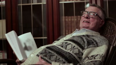 Old man with glasses grandfather reading book aloud in the rocking chair near Stock Footage