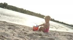 Baby girl one year old playing in the sand on the beach, slow motion Stock Footage