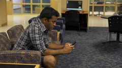 Young Indian man texting in lounge on cell phone 4k Stock Footage