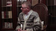 Old man with glasses cheerful grandfather remembers the youth on a rocking chair Stock Footage