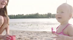 Happy mom and baby girl playing on the beach, clap their hands and laugh Stock Footage