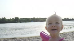 Happy baby girl having fun, smiling and clapping hands on the beach at sunset - stock footage