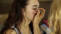 Makeup artist paints the eyebrows of a beautiful girl model using brush Stock Footage