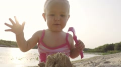 Slow motion happy baby girl destroys sand figure on the beach and have fun - stock footage
